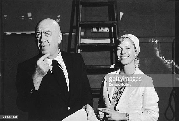 Austrianborn American film actor and director Otto Preminger makes a face and gestures as he holds a document and stands next to Swedish actress Bibi...