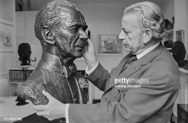 Austrian-born British artist and sculptor William Timym with his bronze bust of conductor Sir Malcolm Sargent, UK, 28th May 1974.