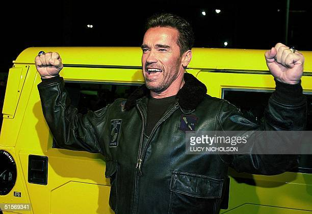 Austrianborn US actor Arnold Schwarzenegger poses by his yellow Hummer car as he arrives at the premiere of his new film The 6th Day in Los Angeles...