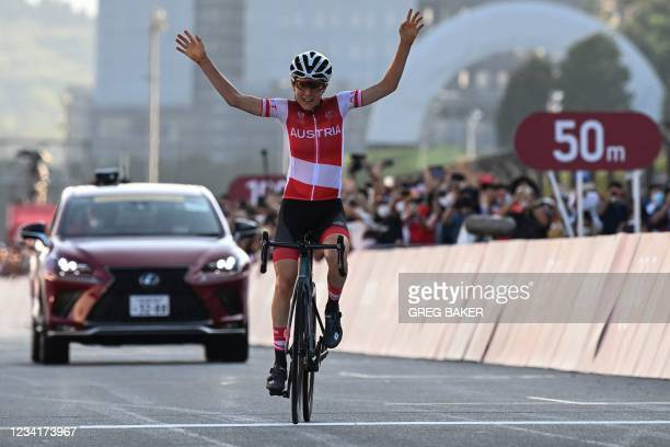 Austria's Anna Kiesenhofer celebrates as she crosses the finish line to win the women's cycling road race of the Tokyo 2020 Olympic Games at the Fuji...