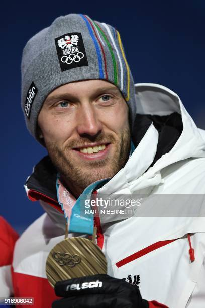 Austria's bronze medallist Dominik Landertinger poses on the podium during the medal ceremony for the men's biathlon individual 20km at the...