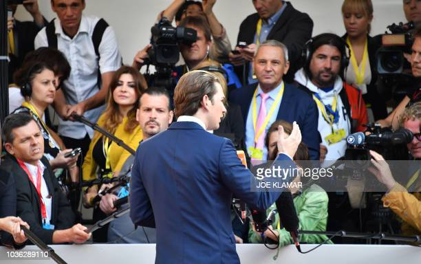 Austria's Chancellor Sebastian Kurz talks with journalists as he arrives at the Mozarteum University to attend a plenary session part of the EU...