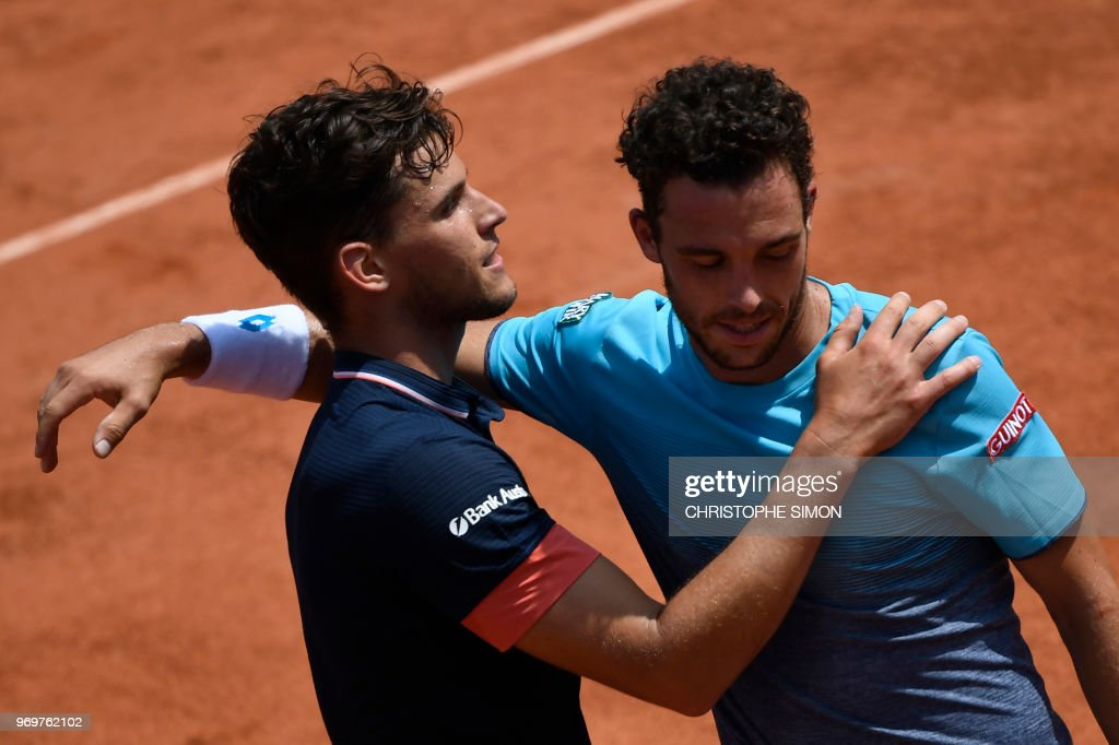 TOPSHOT - Austria's Dominic Thiem (L) embraces as he celebrates after victory over Italy's Marco Cecchinato (R) in their men's singles semi-final match on day thirteen of The Roland Garros 2018 French Open tennis tournament in Paris on June 8, 2018.