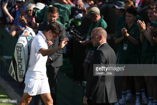 Austria's Dominic Thiem leaves the court after retiring against Cyprus' Marcos Baghdatis during their men's singles first round match on the second...