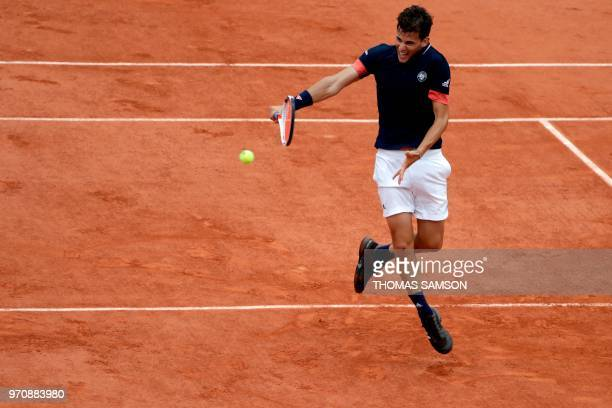 TOPSHOT Austria's Dominic Thiem plays a backhand return to Spain's Rafael Nadal during their men's singles final match on day fifteen of The Roland...