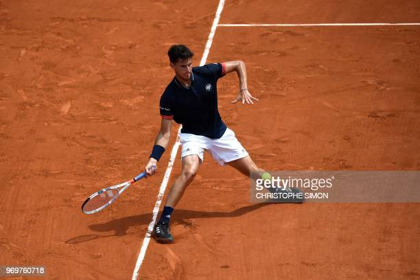 Austria's Dominic Thiem plays a forehand return to Italy's Marco Cecchinato during their men's singles semifinal match on day thirteen of The Roland...