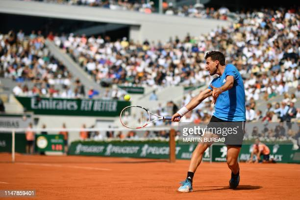 Austria's Dominic Thiem returns the ball to France's Gael Monfils during their men's singles fourth round match on day nine of The Roland Garros 2019...