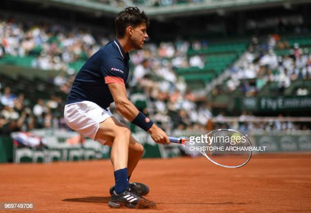 Austria's Dominic Thiem returns the ball to Italy's Marco Cecchinato during their men's singles semifinal match on day thirteen of The Roland Garros...