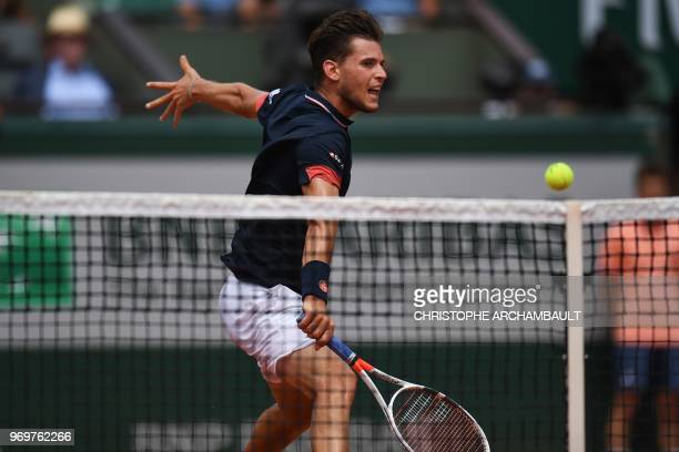 TOPSHOT Austria's Dominic Thiem returns the ball to Italy's Marco Cecchinato during their men's singles semifinal match on day thirteen of The Roland...
