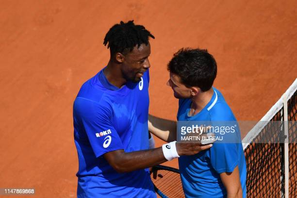 Austria's Dominic Thiem shakes hands with France's Gael Monfils after winning during their men's singles fourth round match on day nine of The Roland...
