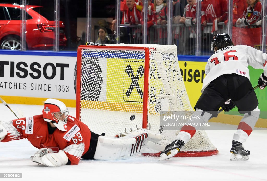 Austria's Dominic Zwerger (R) shoots to score past Switzerland's goalie Leonardo Genoni during the group A match Switzerland vs Austria of the 2018 IIHF Ice Hockey World Championship at the Royal Arena in Copenhagen, Denmark, on May 5, 2018.