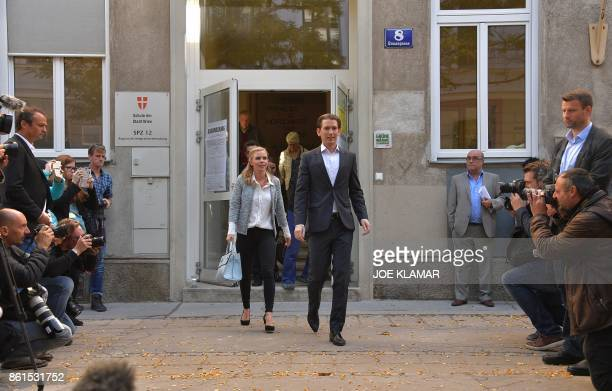Austria's Foreign Minister and leader of Austria's centreright People's Party Sebastian Kurz and his partner Susanne Thier leave a polling station...