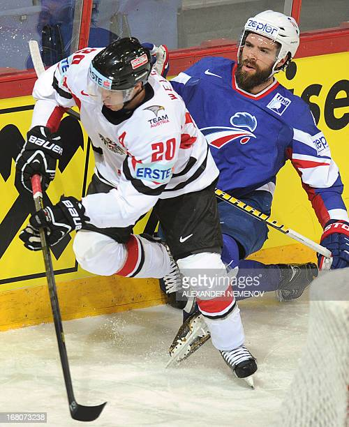 Austria's forward Daniel Welser vies with French defender Antonin Manavian during the preliminary round match France vs Austria at the IIHF...