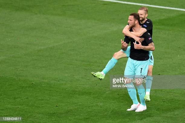 Austria's forward Marko Arnautovic celebrates scoring his team's third goal with his teammates during the UEFA EURO 2020 Group C football match...