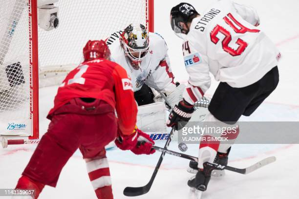 Austria's goalkeeper Bernhard Starkbaum and Austria's defender Steven Strong vie for the puck with Russia's forward Yevgeni Malkin during the IIHF...