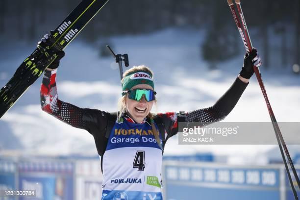 Austria's Lisa Theresa Hauser celebrates as she crosses the finish line to win the Women's 12,5 km Mass Start event at the IBU Biathlon World...