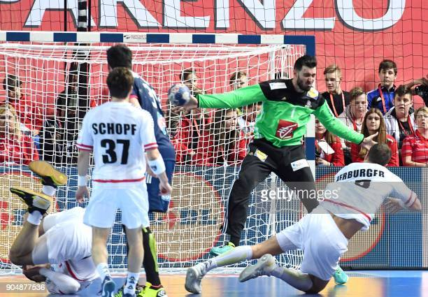 Austria's Lukas Herburge shoots in front of France's goalkeeper Cyril Dumoulin during the preliminary round group B match of the Men's 2018 EHF...
