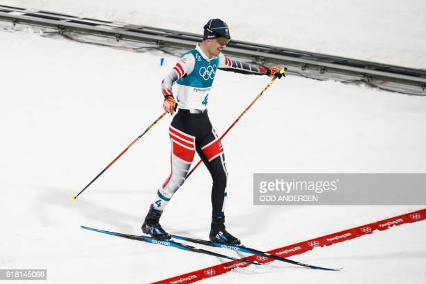 Austria's Lukas Klapfer crosses the finish line to win bronze in the nordic combined men's individual normal hill NH/10km cross country final at the...
