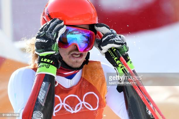 Austria's Manuel Feller reacts after falling just before crossing the finish line in the Men's Giant Slalom at the Jeongseon Alpine Center during the...