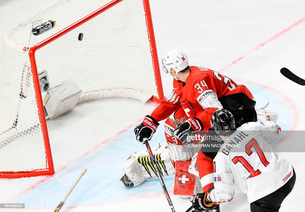 Austria's Manuel Ganahl (R) shoots to score past Switzerland's goalie Leonardo Genoni (L, hidden) as Switzerland's Dean Kukan (C) looks on during the group A match Switzerland vs Austria of the 2018 IIHF Ice Hockey World Championship at the Royal Arena in Copenhagen, Denmark, on May 5, 2018.