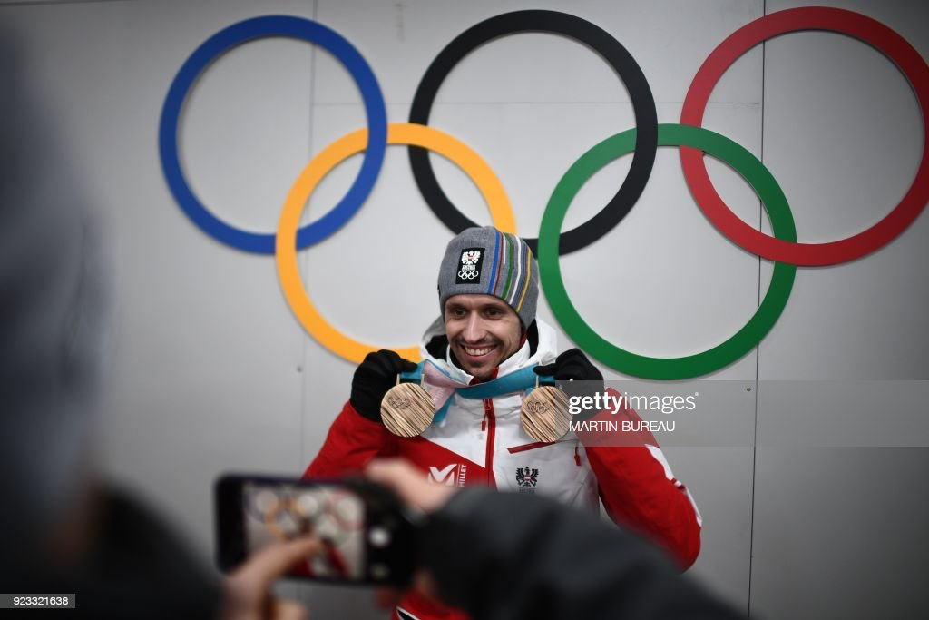 Austria's medallist Lukas Klapfer poses for a picture with his bronze medals in front of Olympic rings backstage at the Athletes' Lounge during the medal ceremonies at the Pyeongchang Medals Plaza during the Pyeongchang 2018 Winter Olympic Games in Pyeongchang on February 23, 2018. / AFP PHOTO / Martin BUREAU