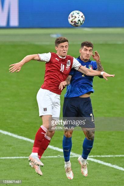 Austria's midfielder Christoph Baumgartner and Italy's defender Giovanni Di Lorenzo vie for the ball during the UEFA EURO 2020 round of 16 football...