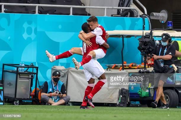Austria's midfielder Christoph Baumgartner celebrates with Austria's defender David Alaba after scoring the opening goal during the UEFA EURO 2020...
