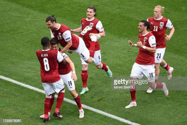 Austria's midfielder Christoph Baumgartner celebrates withg teammates after scoring the opening goal during the UEFA EURO 2020 Group C football match...