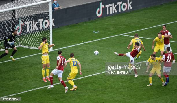 Austria's midfielder Christoph Baumgartner shoots and scores the opening goal during the UEFA EURO 2020 Group C football match between Ukraine and...