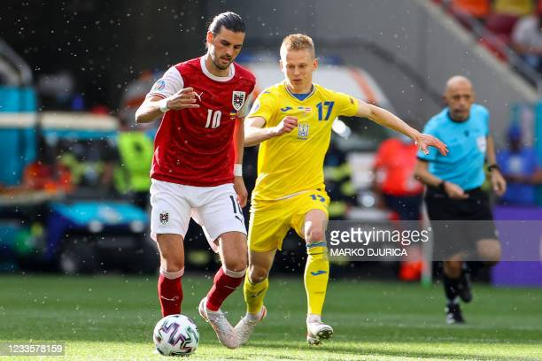 Austria's midfielder Florian Grillitsch fights for the ball with Ukraine's defender Oleksandr Zinchenko during the UEFA EURO 2020 Group C football...