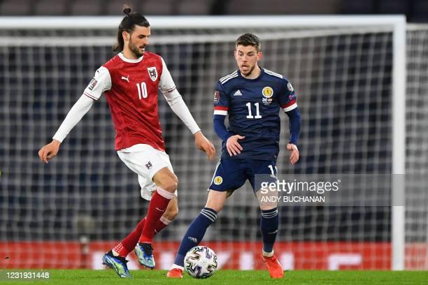 Austria's midfielder Florian Grillitsch vies with Scotland's striker Ryan Christie during the FIFA World Cup Qatar 2022 qualification football match...
