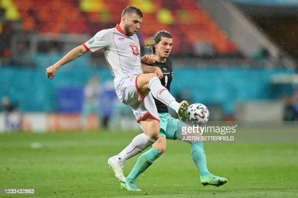 Austria's midfielder Marcel Sabitzer challenges North Macedonia's defender Stefan Ristovski during the UEFA EURO 2020 Group C football match between...
