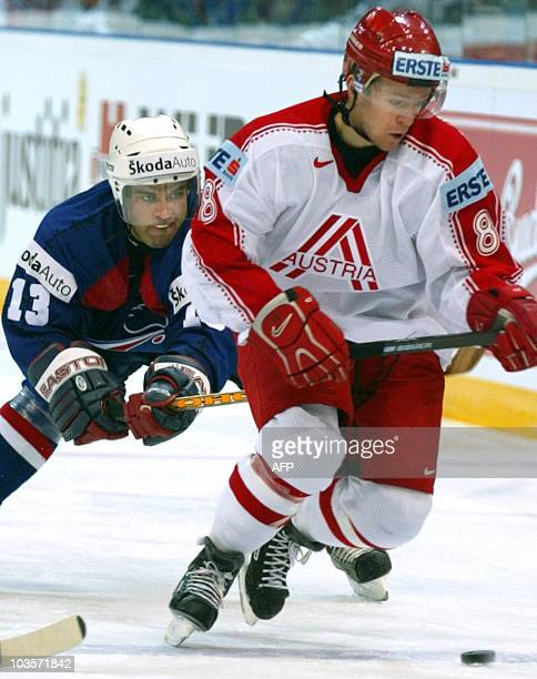 Austria's Philippe Horsky fights for the puck with France's Jonatan Zwikel during their Group D match at the 2004 International Ice Hockey World...