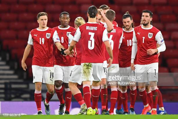 Austria's players celebrate their first goal during the FIFA World Cup Qatar 2022 qualification football match between Scotland and Austria at...