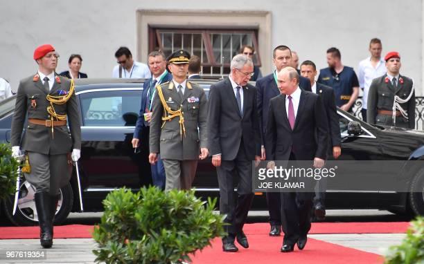Austria's President Alexander van der Bellen and Russian President Vladimir Putin arrive to inspect a military honor guard at the Presidential palace...