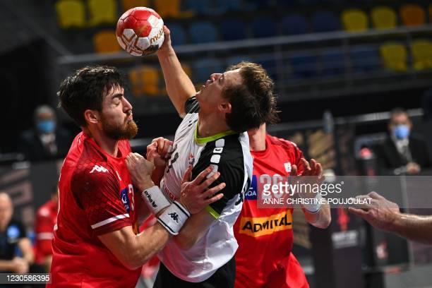 Austria's right back Boris Zivkovic challenges Switzerland's left back Roman Sidorowicz during the 2021 World Men's Handball Championship between...