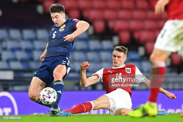 Austria's striker Saa Kalajdi? is booked for this tackle on Scotland's defender Kieran Tierney during the FIFA World Cup Qatar 2022 qualification...