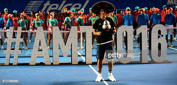 Austria´s tennis player Dominic Thiem wears a traditional Mexican mariachi hat while holding the winning trophy after defeating Australia's Bernard...
