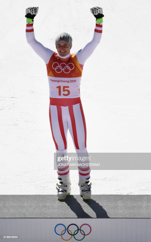 Austria's winner Matthias Mayer celebrates on the podium during the victory ceremony at the end of the Men's Super-G at the Jeongseon Alpine Center during the Pyeongchang 2018 Winter Olympic Games in Pyeongchang on February 16, 2018. / AFP PHOTO / Jonathan NACKSTRAND