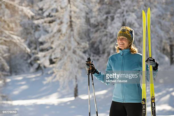 Austria, Tyrol, Seefeld, Wildmoosalm, Woman holding cross-country skis, close-up