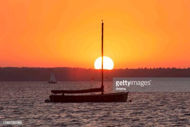 Auswanderer, traditional wooden sailing boat in Steinhuder Meer / Lake Steinhude silhouetted against sunset, Lower Saxony / Niedersachsen, Germany.