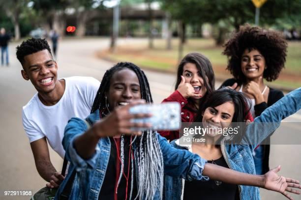 autêntico grupo de diversos amigos tomando uma selfie no parque - camera girls - fotografias e filmes do acervo