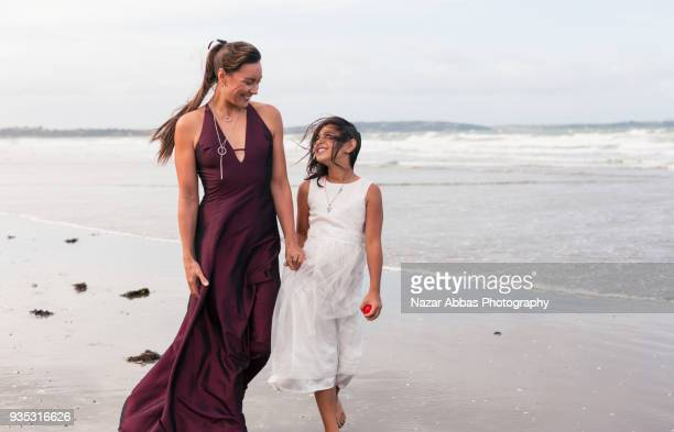 Authentic moment between mother and daughter walking on beach.