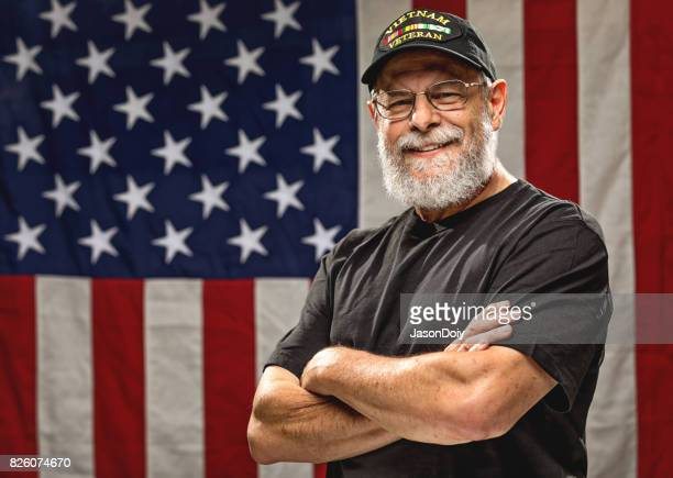 authentic vietnam veteran with american flag - armistice day stock photos and pictures