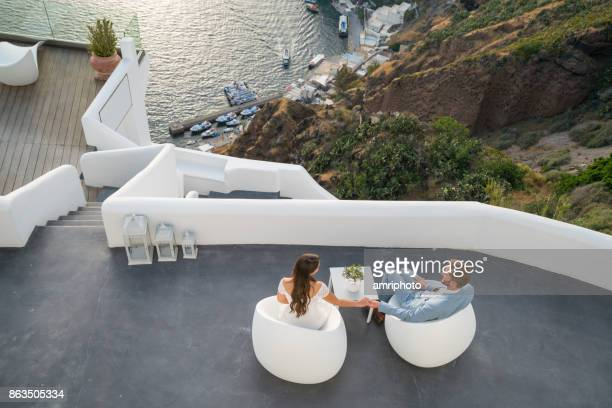 Authentic Wealth - couple sittging on terrace on santorini island