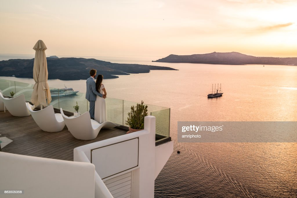Authentic Wealth - rich couple standing on terrace with amazing sea view : Stock Photo