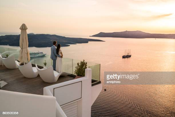 authentic wealth - rich couple standing on terrace with amazing sea view - honeymoon stock pictures, royalty-free photos & images