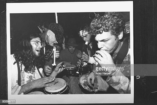 Author '60s guru Ken Kesey playing the flute w four Hofstra Univ students who are playing flutes bongo drums outside his home the students are part...