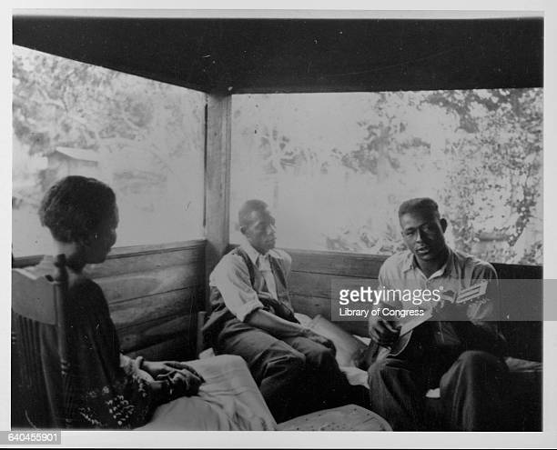 Author and anthropologist Zora Neale Hurston sitting on a porch in Eatonville Florida with two musicians Rochelle French and Gabriel Brown