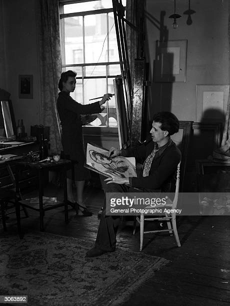 Author and illustrator Mervyn Peake sketches a likeness of his wife painter Maeve Gilmour while she is working at her easel